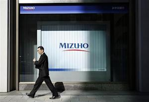 A man walks past a branch of Mizuho bank belonging to Mizuho Financial Group in Tokyo