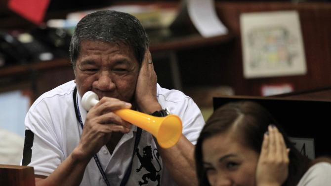 A trader blows a horn as his colleague reacts at the trading floor of the Philippine Stock Exchange in Makati city