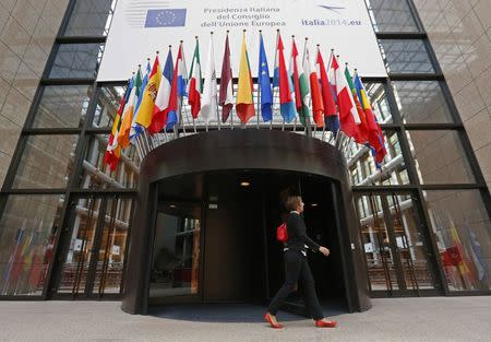 A woman walks past the entrance of the European Council headquarters in Brussels
