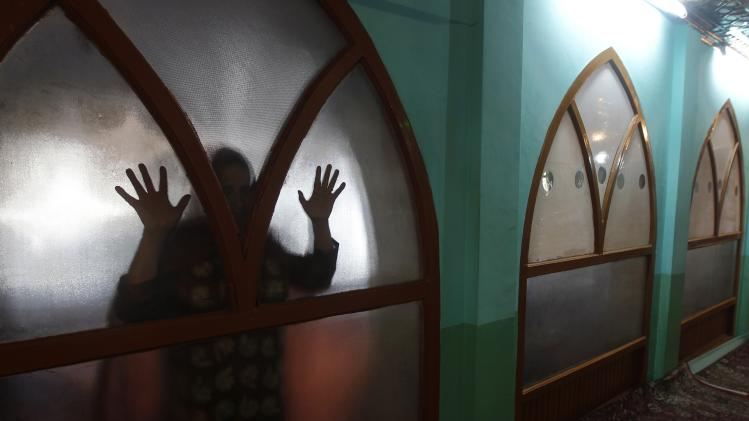 A Kashmiri Muslim woman prays behind a glass window, as women are not allowed to enter, at the shrine of Sufi saint Ziarat Sharief Hazrat Syed Yaqoob Sahib, during the holy month of Ramadan in Srinagar