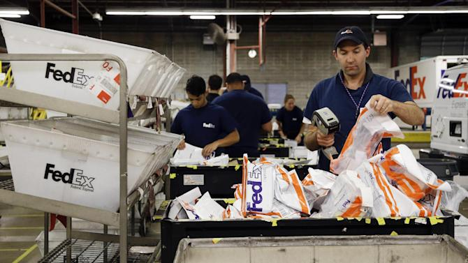 In this July 9, 2014 photo, David Demeter sorts packages at the FedEx Express station in Nashville, Tenn. FedEx on Wednesday, Oct. 22, 2014 forecast that deliveries between Thanksgiving and Christmas Eve will rise 8.8 percent over last year, to 290 million shipments. That's a more subdued forecast than a year ago, when FedEx predicted 13 percent growth for the season. (AP Photo/Mark Humphrey)