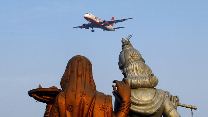 Statue of Hindu Gods Radha, left, and Krishna stand in the foreground as a Kingfisher Airlines flight approaches the Indira Gandhi International airport in New Delhi, India, Friday, Nov. 11, 2011. Kingfisher, which is partly owned by brewery tycoon Vijay Mallya, has canceled more than 120 flights this week as pilots and crew called in sick after their October salaries were delayed. (AP Photo/Gurinder Osan)