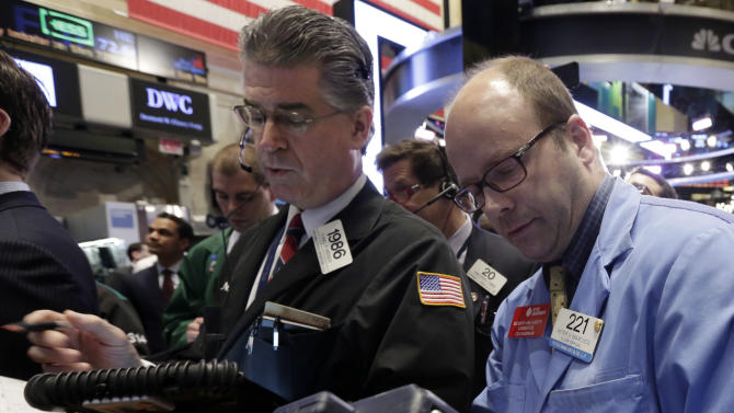 In this  Friday, April 12, 2013, photo, traders Daniel Kryger, left, and Peter Mancuso work on the floor of the New York Stock Exchange.  (AP Photo/Richard Drew)