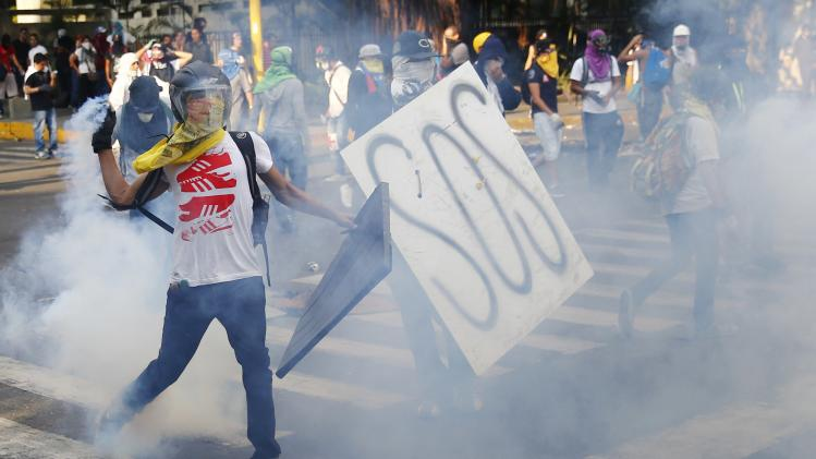 An anti-government protester throws a teargas canister back at policemen during a riot in Caracas