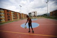 A boy plays with a ball in Ciudad Caribia outside Caracas September 19, 2013. REUTERS/Jorge Silva