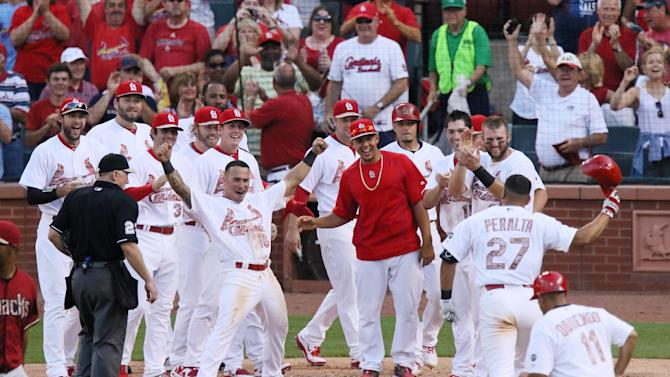 St. Louis Cardinals' Jhonny Peralta (27) is greeted by teammates at home plate after hitting a walk-off solo home run in the tenth inning during a game between the St. Louis Cardinals and the Arizona Diamondbacks on Monday, May 25, 2015, at Busch Stadium in St. Louis. (/St. Louis Post-Dispatch via AP)  EDWARDSVILLE INTELLIGENCER OUT; THE ALTON TELEGRAPH OUT; MANDATORY CREDIT   Photo by Chris Lee, clee@post-dispatch.com