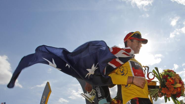 Tour de France winner Cadel Evans of Australia, wearing the overall leader's yellow jersey and draped in the Australian national flag leaves the podium in Paris, France, Sunday July 24, 2011. (AP Photo/Christophe Ena)