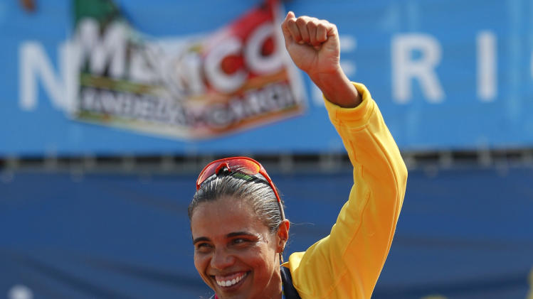 Mexico's silver medalist Bibiana Candelas, carries on her back Brazil's Juliana Silva, gold medalist, at the podium during the award ceremony of the women's beach volleyball event at the Pan American Games in Puerto Vallarta, Mexico, Friday, Oct. 21, 2011.(AP Photo/Ariana Cubillos)