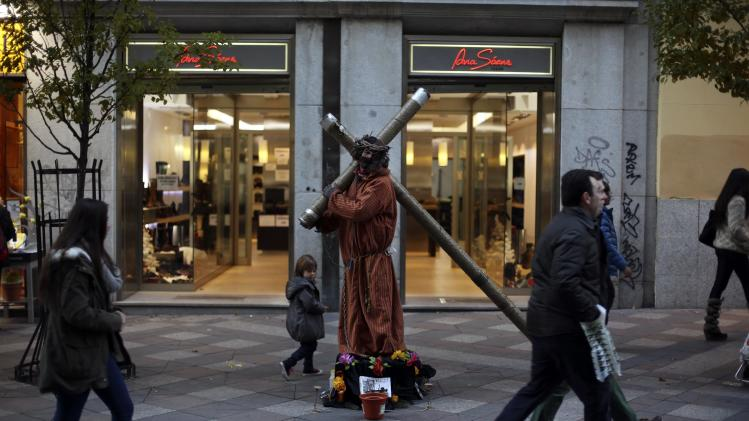 People walk past a street performer dressed as Jesus Christ outside an empty store in central Madrid