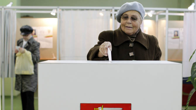 An elderly woman votes at a polling station in Vilnius, Lithuania, Sunday, Oct. 28, 2012. Lithuanians balloted Sunday in a second round of parliamentary elections.  (AP Photo/Mindaugas Kulbis)