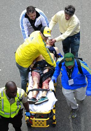 Medical workers aid an injured man at the finish line of the 2013 Boston Marathon following an explosion in Boston, Monday, April 15, 2013. Two bombs exploded near the finish of the Boston Marathon on Monday, killing two people, injuring 22 others and sending authorities rushing to aid wounded spectators, race organizers and police said. (AP Photo/Charles Krupa)