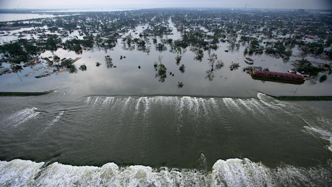 FILE - In this Aug. 30, 2005 file photo, floodwaters from Hurricane Katrina pour through a levee along Inner Harbor Navigational Canal near downtown New Orleans, La., a day after Katrina passed through the city. (AP Photo/Vincent Laforet, Pool, File)