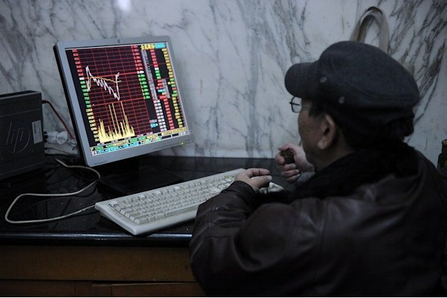 An investor looks at stock prices on a screen at a securities exchange in Shanghai on March 4, 2013