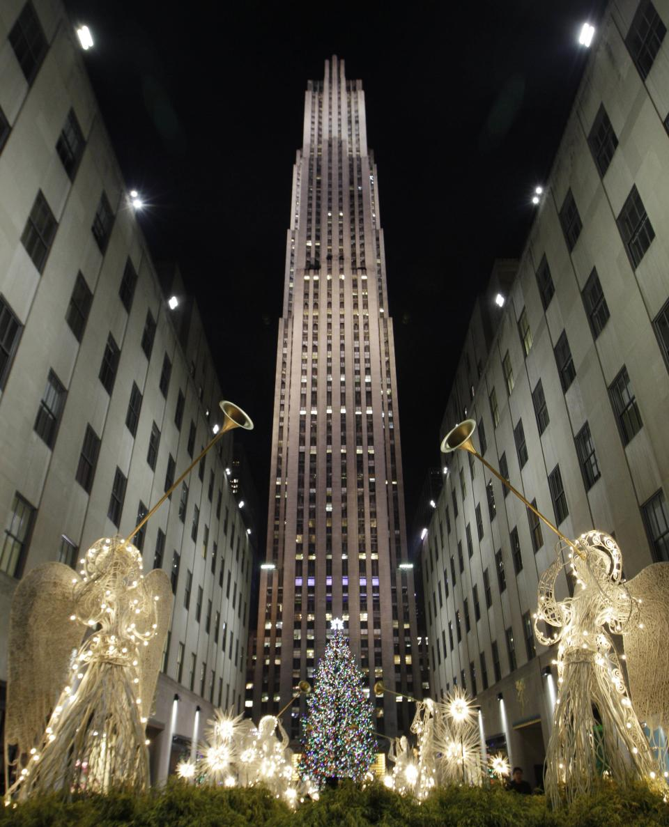 Angels in lights frame the Rockefeller Center Christmas tree as seen from the Channel Gardens after the tree was lit during the 80th annual tree lighting ceremony at Rockefeller Center in New York, Wednesday, Nov. 28, 2012.  (AP Photo/Kathy Willens)