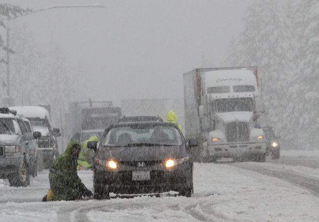 Chain installers work as snow falls on eastbound Interstate 80 near Nyack, Calif., Monday, Oct. 22, 2012. The first storm of the season swept through Northern California bringing rain to the lower elevations and snow in the mountains. (AP Photo/Rich Pedroncelli)