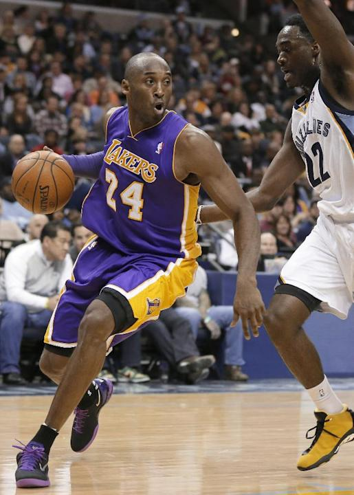 In this Dec. 17, 2013, file photo, Los Angeles Lakers' Kobe Bryant (24) dribbles around Memphis Grizzlies' Jamaal Franklin (22) during the first half of an NBA basketball game in Memphis, Tenn