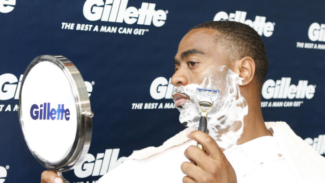 COMMERCIAL IMAGE - American 100m record holder Tyson Gay is seen shaving his beard after presenting his former high school coach Ken Northington with a $25,000 Great Start grant to support the next generation of men at Gillette World Shaving Headquarters, Monday, June 11, 2012, in Boston. The grant will support the track and field team at Lafayette High School in Lexington, KY., where Gay got his great start. (Photo by Bizuayehu Tesfaye/Invision for Gillette/AP Images)