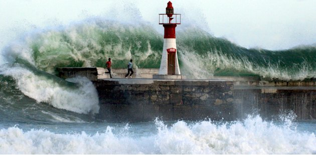 Giant waves crash over onlookers …
