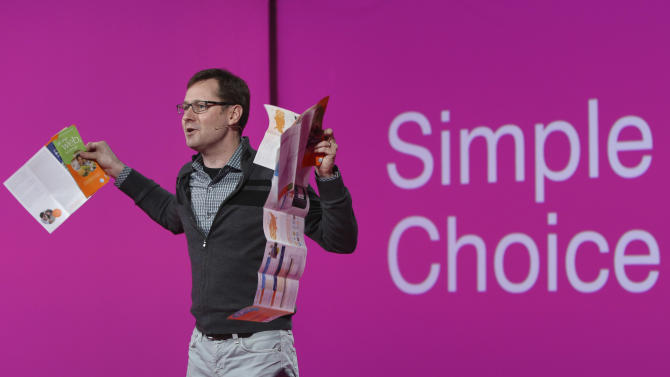 "T-Mobile  Chief Marketing Officer Mike Sievert holds brochures if competitors' plans as he speaks during a news conference, Tuesday, March 26, 2013 in New York. T-Mobile will start offering the iPhone 5 on April 12, filling what company CEO John Legere said was ""a huge void"" in its phone lineup. The company is currently the only major U.S. carrier not to offer Apple's popular smartphone. (AP Photo/Mary Altaffer)"