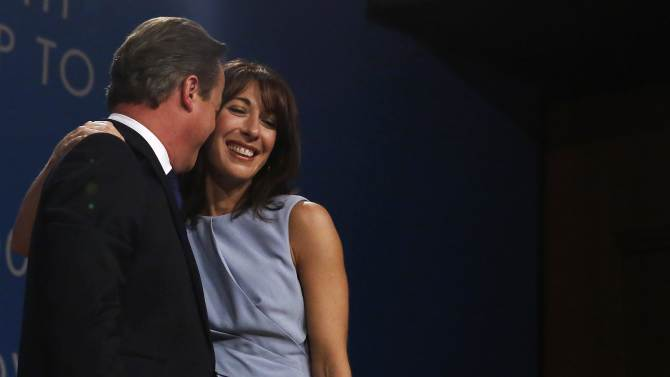 Britain's Prime Minister David Cameron embraces his wife Samantha after delivering his keynote address to the Conservative Party Conference in Birmingham, central England