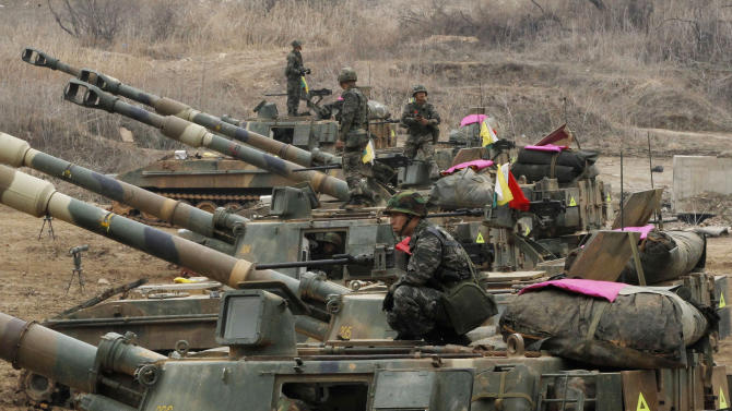 A South Korean marine sits on a K-55 self-propelled howitzer during an exercise against possible attacks by North Korea near the border village of Panmunjom in Paju, South Korea  Monday, April 1, 2013. After weeks of war-like rhetoric, North Korean leader Kim Jong Un gathered legislators Monday for an annual spring parliamentary session taking place one day after top party officials adopted a statement declaring building nuclear weapons and the economy the nation's top priorities.(AP Photo/Ahn Young-joon)