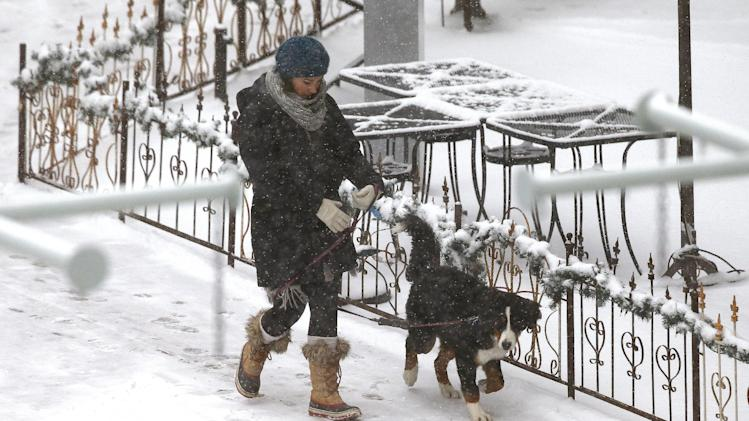 A woman walks with a dog as temperatures hovered around 8 degrees Wednesday Dec. 4, 2013, in Denver. A wintry storm pushing through the Rockies and Midwest is bringing bitterly cold temperatures and treacherous driving conditions. (AP Photo/Brennan Linsley)