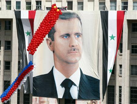 A larger banner of Syrian President Bashar al-Assad hangs from central bank during a rally of his supporters at al-Sabaa Bahrat square in Damascus