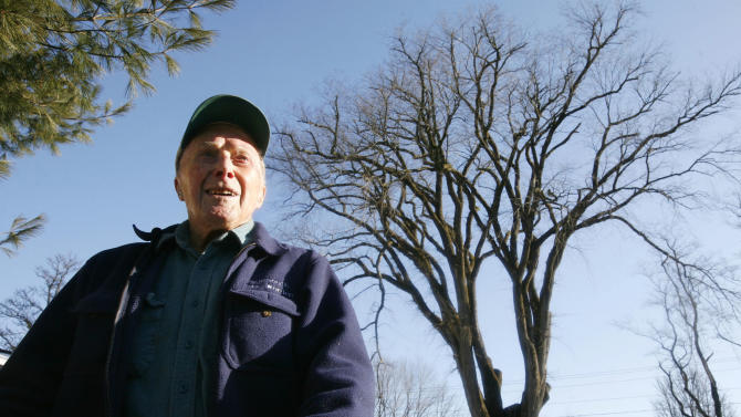 "FILE - In this Dec. 14, 2009 file photo, Frank Knight stands in front of New England's tallest elm tree, known as ""Herbie,"" in Yarmouth, Maine. Knight, who took care of the tree for five decades while working as the Yarmouth tree warden, died in Scarborough, Maine, Monday, May 14, 2012. He was 103. (AP Photo/Steven Senne, File)"