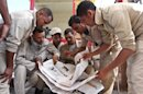 Egyptian border policeman read an Egyptian newspaper reporting on the abduction of their colleagues last Thursday, at the closed Rafah border crossing between Egypt and the Gaza strip, in Rafah, Egypt, Monday, May 20, 2013. Security officials said 17 military and more than 20 police armored vehicles were deployed in northern Sinai Monday as a response to the kidnapping by suspected militants of six policemen and a border guard there last Thursday. It was not clear if they deployed to rescue the hostages, to make a show of force to intimidate their captors, or for another reason. (AP Photo/Roger Anis, El Shorouk Newspaper) EGYPT OUT