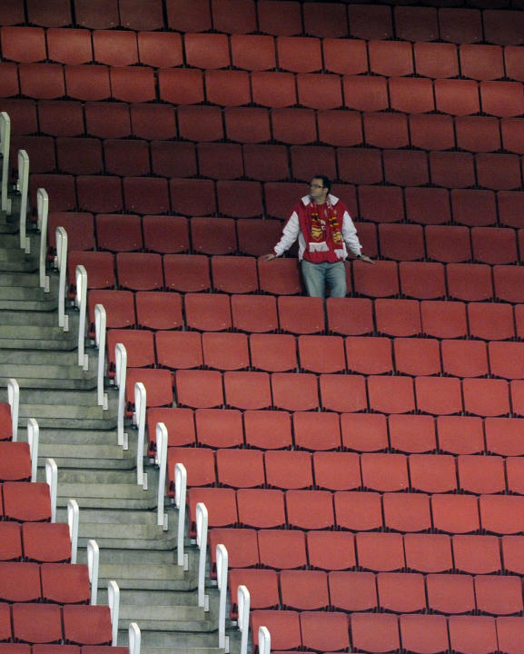A fan waits for the start of the English League Cup soccer match between Arsenal and Shrewsbury Town at the Emirates stadium, London, Tuesday, Sept. 20, 2011. (AP Photo/Tom Hevezi)