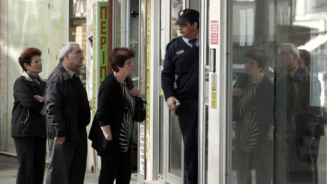 A security guard opens the entrance of a Laiki bank branch as people queue in capital Nicosia, on Friday, March 29, 2013. Banks in Cyprus are open for normal business for the second day, but with strict restrictions on how much money their clients can access, after being shut for nearly two weeks to prevent people from draining their accounts as the country's politicians sought a way out of an acute financial crisis. (AP Photo/Petros Giannakouris)