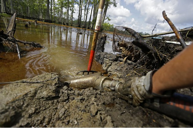 In this Thursday, June 27, 2013 photo, contractors use a vacuum truck to clean up crude oil that has risen to the surface of an approximate 22-acre sinkhole in Bayou Corne, La. Neighbors in tiny Bayou