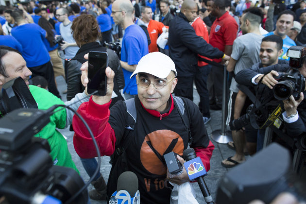 Hazem Sayed, 54, the first in line to purchase the new iPhone 5, holds up his new phone in front of media outside the Fifth Avenue Apple store, Friday, Sept. 21, 2012, in New York. Hundreds of people