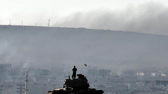A Turkish soldier stands on a tank as he observes the Syrian town of Ain al-Arab, known as Kobane by the Kurds, from a hill at the Turkish-Syrian border on October 9, 2014