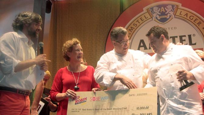 IMAGE DISTRIBUTED FOR RED ROBIN - Mo Rocca, far left,  host of Cooking Channel's My Grandmother's Ravioli and correspondent for CBS Sunday Morning with Charles Osgood,  Denny Marie Post, Red Robin chief menu and marketing officer, Scott Weaver, Red Robin director of culinary, and Laurent Tourondel of LT Burger in the Harbor, right,  announced LT Burger in the Harbor as Red Robin's Best of the Bash Award for their Smashed Smoke Burger at the Amstel Light Burger Bash at the Food Network South Beach Wine and Food Festival on Feb. 22, 2013.  Rocca helped judge the contest and the Smashed Smoke Burger was declared the winner for its craveable combination of black peppered bacon, New York State cheddar, Spanish onion and sweet sauce.  (Photo by Marianela Sanchez/Invision for Red Robin/AP Images)