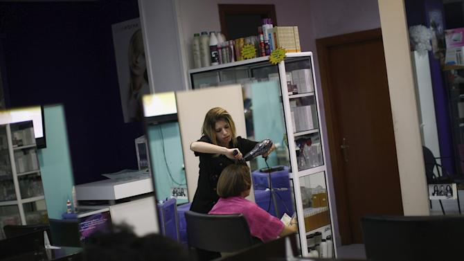 Desire Vargas, 20, is reflected in a mirror as she combs a customer's hair at a hairdressing salon where she studies a course in beauty and hairdressing in downtown Ronda, near Malaga, southern Spain