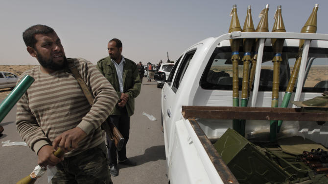 A Libyan rebel arms ammunitions after retreating back east at the outskirts of the town of al-Agila, Libya Wednesday, March 30, 2011. Moammar Gadhafi's ground forces recaptured a strategic oil town Wednesday and were close to taking a second, making new inroads in beating back a rebel advance toward the capital Tripoli. (AP Photo/Nasser Nasser)