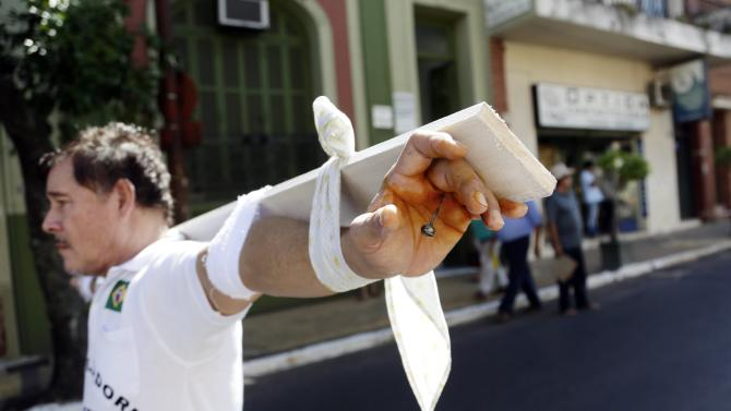 Roberto Gonzalez a former worker of Unicom and Conempa, Paraguayan Itaipu Dam contractors, walks in the streets of Asuncion towards the Ministry of labor, in a symbolic crucifixion, in Paraguay, Monday, Jan. 26, 2015. Gonzalez  is part of a group that for the last 25 years, after the construction on the dam was completed, is demanding compensation benefits from the contractors. The Itaipu hydroelectric dam on the Parana River straddles the Brazil-Paraguay border. (AP Photo/Jorge Saenz)