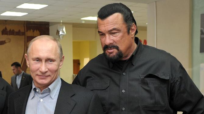 This photo taken on March 13, 2013 shows Russia's President Vladimir Putin and American action movie actor Steven Seagal visiting a newly-built sports complex of Sambo-70 prominent wrestling school in Moscow