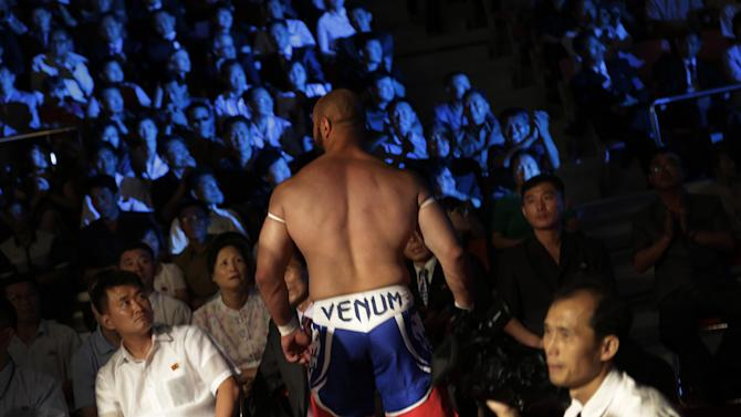 """North Koreans watch a pro-wrestler leave the fighting arena after a match, Saturday, Aug. 30, 2014 in Pyongyang, North Korea. North Koreans got their first look at pro wrestling in about 20-years on Saturday when former NFL lineman Bob """"The Beast"""" Sapp, and 20 other fighters from around the world took to the ring for an exhibition in Pyongyang, put together by colourful Japanese pro-wrestler Kanji """"Antonio"""" Inoki, who is now a member of parliament. (AP Photo/Wong Maye-E)"""