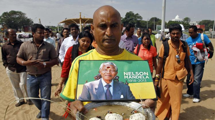 A man carries a portrait of Mandela as he performs Tarpanam, a Hindu ritual to honour the souls of departed ancestors, in Chennai