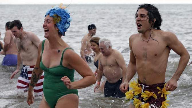 A couple takes the plunge on New Year's Day during the 110th annual Coney Island Polar Bear Club ocean swim at Coney Island in New York, Tuesday, Jan. 1, 2013.  (AP Photo/Kathy Willens)