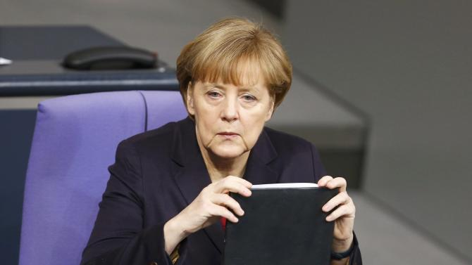 German Chancellor Merkel listens to a speaker during a session of the German lower house of parliament Bundestag in Berlin