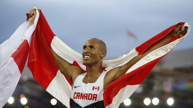 Warner of Canada celebrates finishing first place with the flag in the Men's Decathlon at the Commonwealth Games in Glasgow