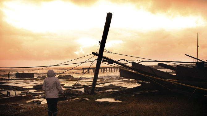 Kim Johnson looks over the destruction near her seaside apartment in Atlantic City, N.J., Tuesday, Oct. 30, 2012. The storm, which made landfall Monday evening, caused multiple fatalities, halted mass transit and cut power to more than 6 million homes and businesses. (AP Photo/Seth Wenig)