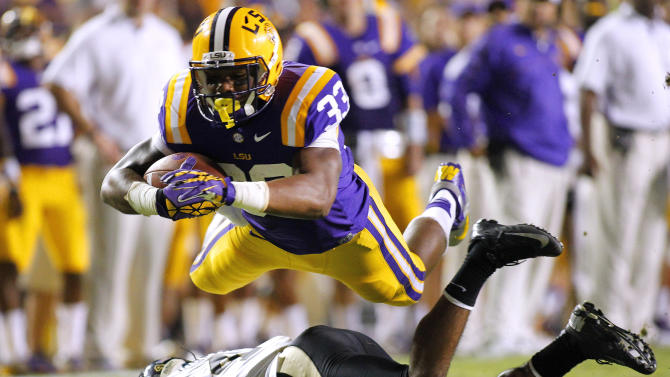 LSU Tigers running back Jeremy Hill dives over Idaho Vandals cornerback Jayshawn Jordan during the second half of their NCAA football game in Baton Rouge, Louisiana