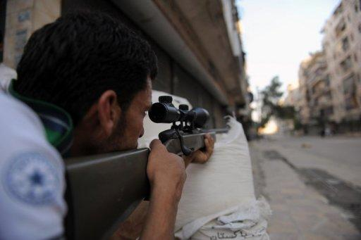 A fighter from the Syrian opposition aims fire during clashes with forces loyal to President Bashar al-Assad in Aleppo
