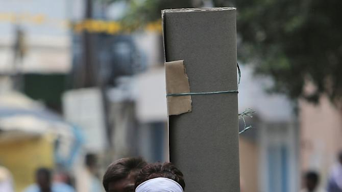 An Indian motorist covers his face with a scarf to protect himself from the heat on a hot summer day in Hyderabad, India, Wednesday, May 27, 2015. Hundreds of people have died in southern India since the middle of April as soaring summer temperatures scorch the country, officials said Tuesday. (AP Photo/Mahesh Kumar A.)