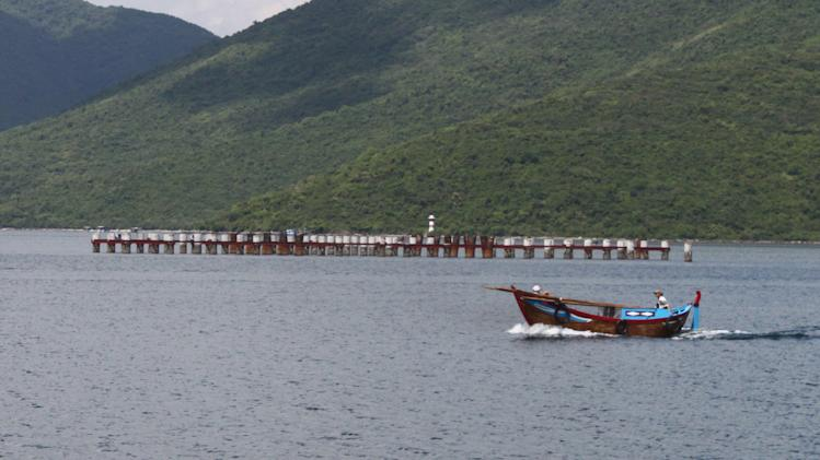 "In this photo taken Oct. 17, 2011, a boat passes by the abandoned Van Phong port in Khanh Hoa provinvce in southern Vietnam. All that remains of a plan by Vietnam to build a major deep water port is 114 exposed pilings trailing into the South China Sea and a barge full of rusty machinery. Foreign investors stayed away from the $3.6 billion project and the indebted state-owned company overseeing it bungled the job. Earlier this month, Sept., 2012, the government accused the company of ""financial incompetence"" and suspended the project. The prospects for ever reviving it are dim. (AP Photo/TuoI Tre Newspaper, Van Ky) VIETNAM OUT"