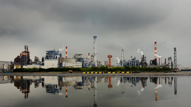 A petrochemical plant is reflected in a puddle at an industrial complex in Kawasaki near Tokyo